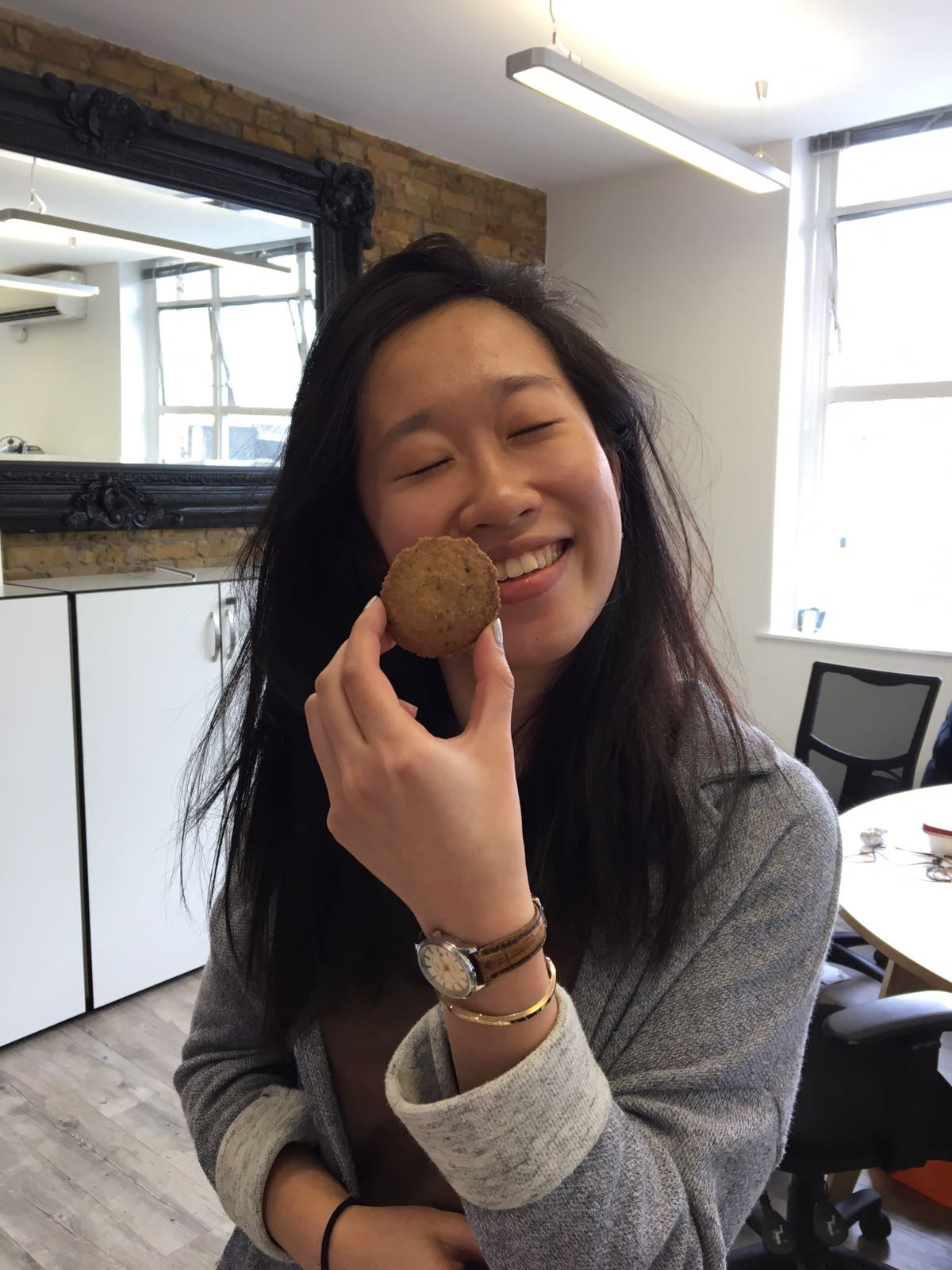 Woman smiling with a cookie held against her face
