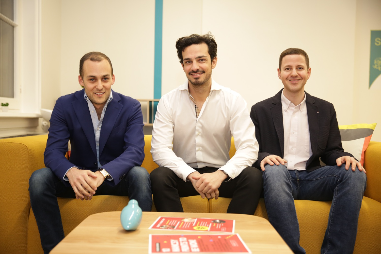 Three well-dressed men sat on a sofa for a photo