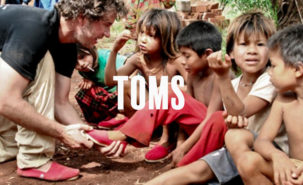The text 'Toms' over the image of a man putting shoes on less privileged kids