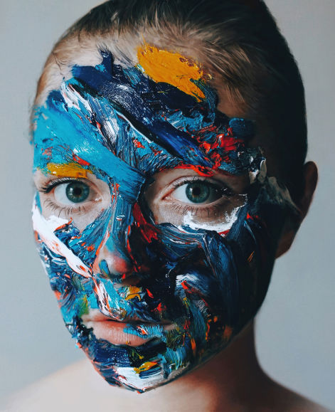 Woman's face painted with a mix of colours