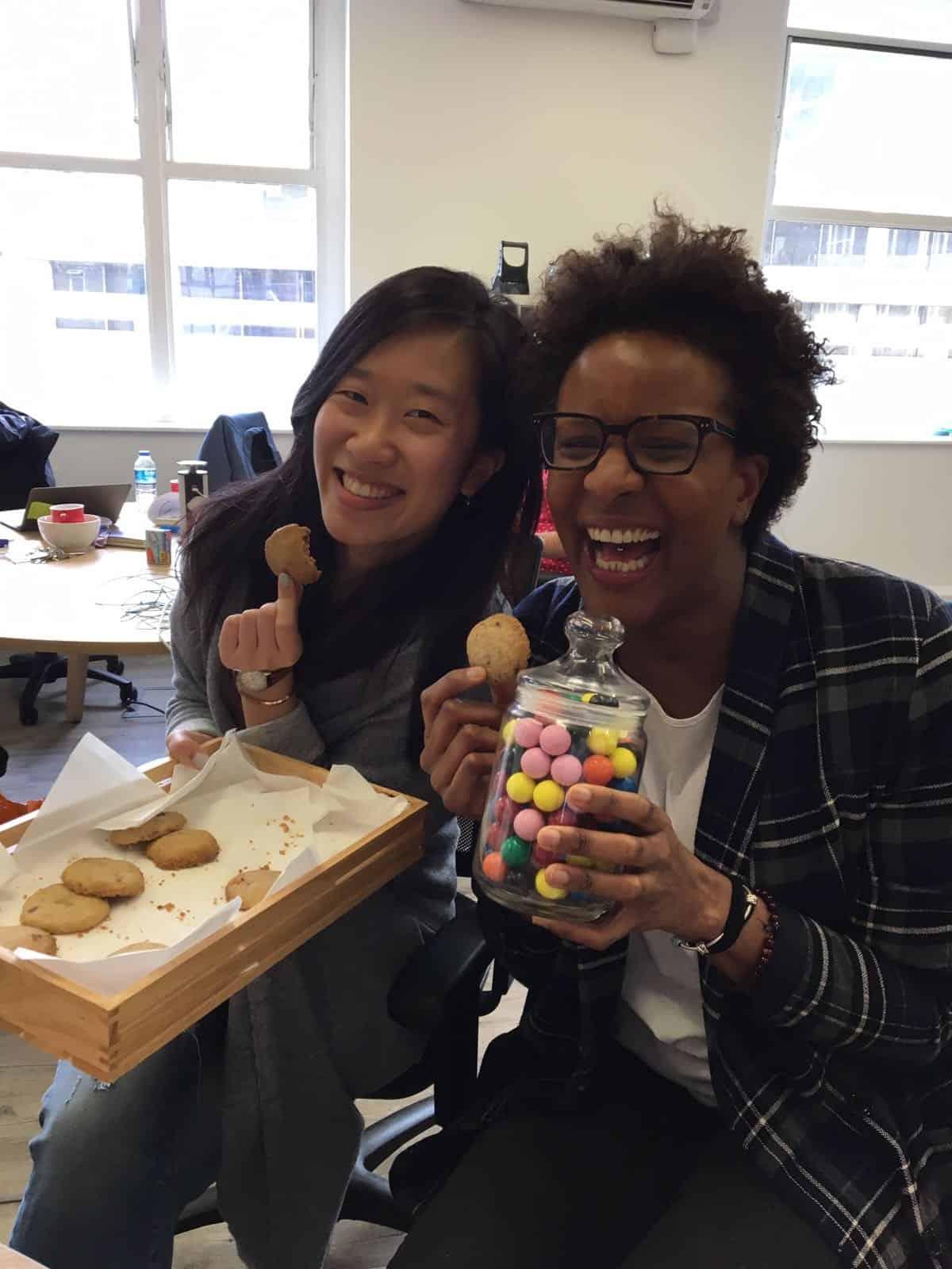 Two people smiling eating cookies