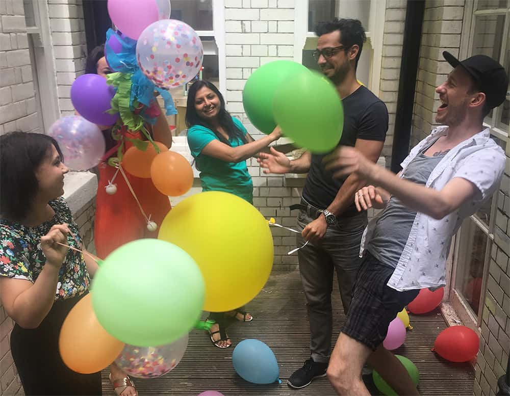 Group of people outside messing around with balloons