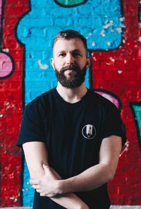Man posing for a photo against a graffiti-ed wall