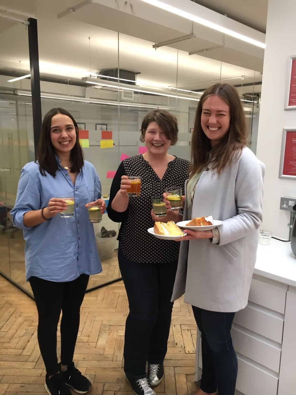 Three women holding drinks and food