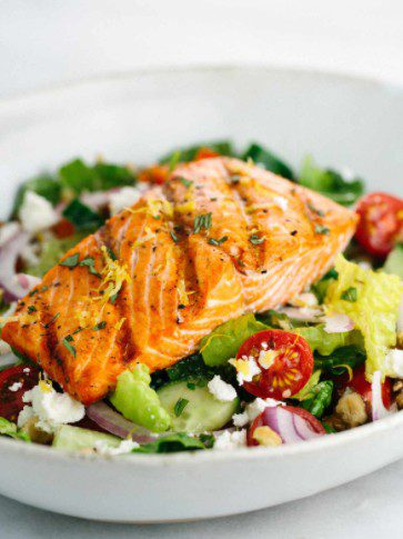 Cooked fish atop a bowl of salad